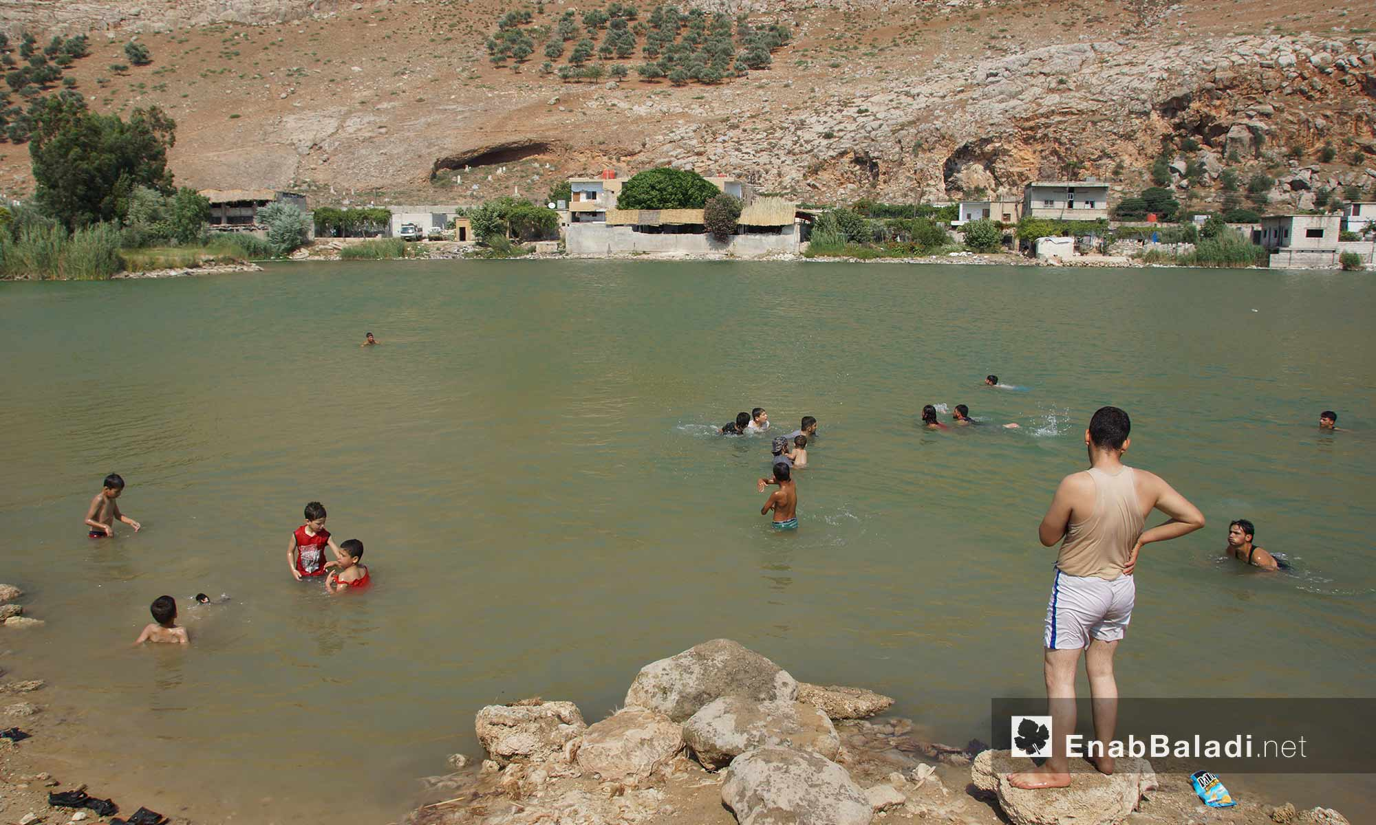 """أطفال وعائلات يسبحون في بحيرة نبع قرية """"باب الطاقة""""  غربي حماة - 13 تموز 2018 (عنب بلدي)"""