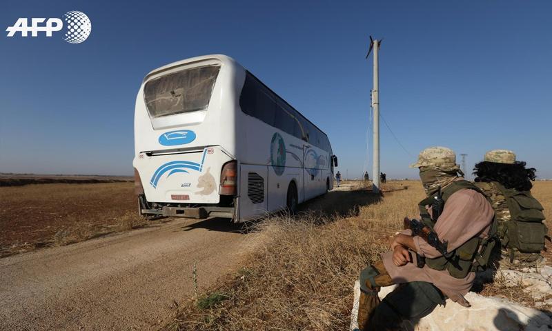 مقاتلان من فصائل المعارضة ينظران إلى حافلات تقل مقاتلي بلدتي كفريا والفوعة - 19 من تموز 2018 (AFP عمر حاج قدور)