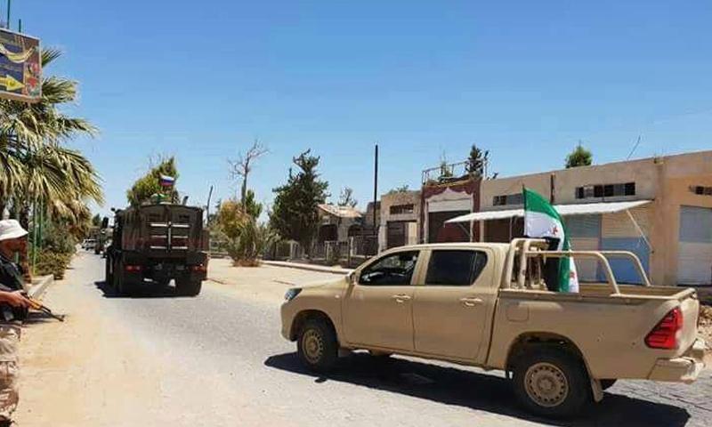 عربة روسية وفي خلفها سيارة تتبع لفصائل الجيش الحر في أثناء توجهها للتفاوض في بصرى الشام - 1 من تموز 2018 (فيس بوك)
