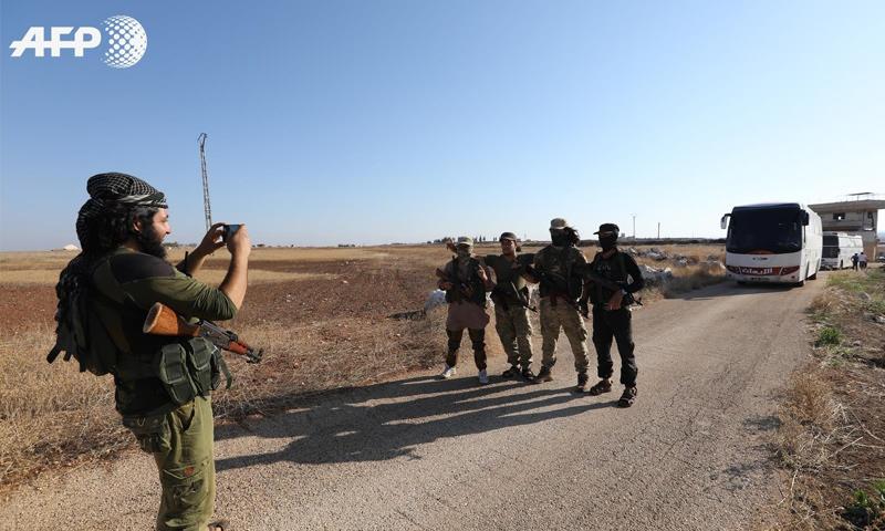 مقاتلون من فصائل المعارضة في أثناء خروج مقاتلي كفريا والفوعة - 18 من تموز 2018 (AFP عمر حاج قدور)