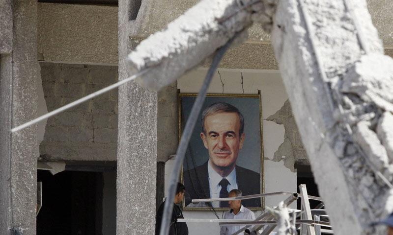 صورة للرئيس السوري السابق معلقة في منزل تتضرر جراء انفجار في دمشق (رويترز)