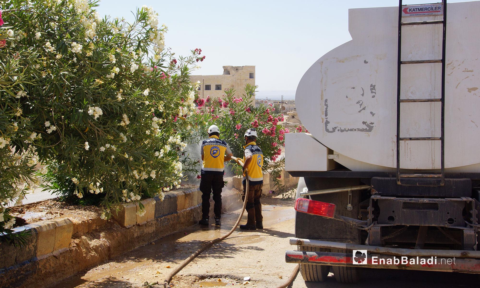 """عناصر من الدفاع المدني يقومون بعملية تنظيف للطرقات ضمن حملة """"إحياء الأرض"""" في مدينة مورك بريف حماة - 7 تموز 2018 (عنب بلدي)"""