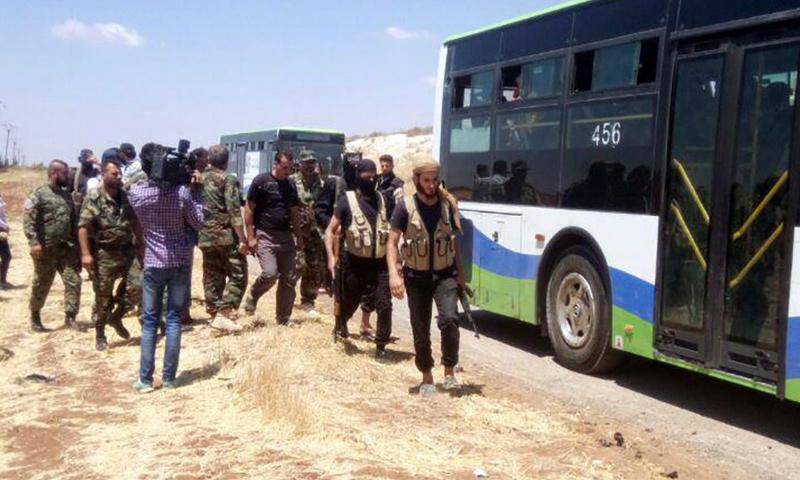 مقاتلون من بلدة محجة في أثناء خروجهم إلى الشمال السوري - 21 من تموز 2018 (سانا)