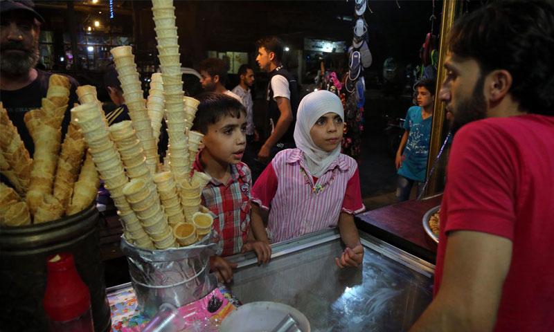 أطفال سوريون يشترون بوظة محلية في الغوطة الشرقية - 4 تموز 2018 (AFP)