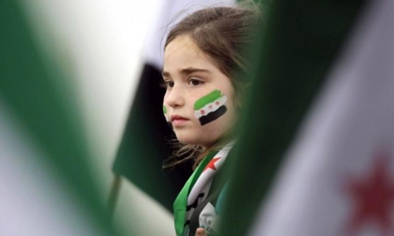 تعبيرة لفتاة ترسم علم الثورة السورية على وجهها