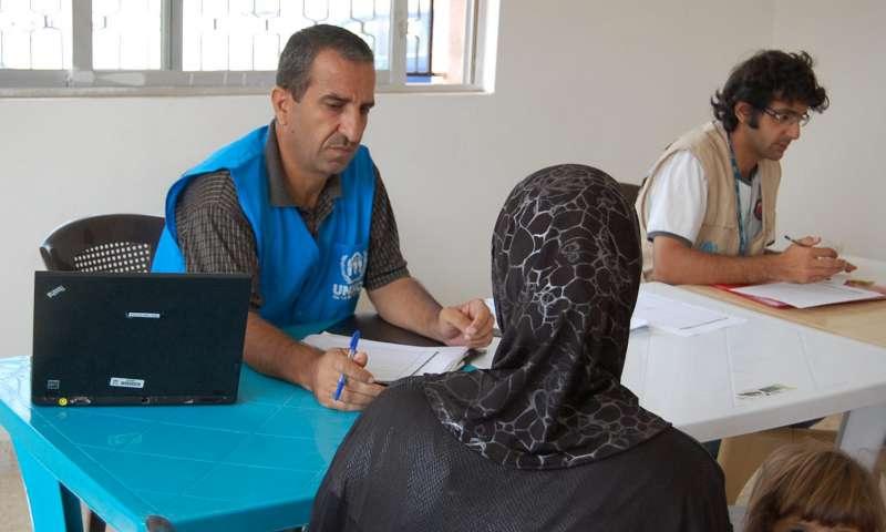 أحد موظفي المفوضية يقوم بتسجيل لاجئة سورية في إربد (UNHCR)