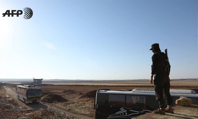 مقاتل من فصائل المعارضة ينظر إلى حافلات تقل مقاتلي بلدتي كفريا والفوعة - 19 من تموز 2018 (AFP عمر حاج قدور)