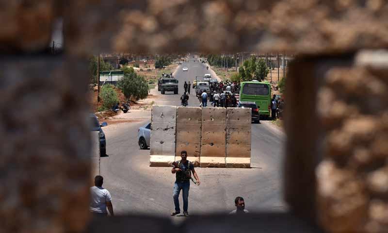 توقف حافلة عند نقطة تفتيش في أثناء عودة نازحين من محافظة درعا إلى بلدتهم في بصرى الشام - 11 تموز 2018 (AFP)