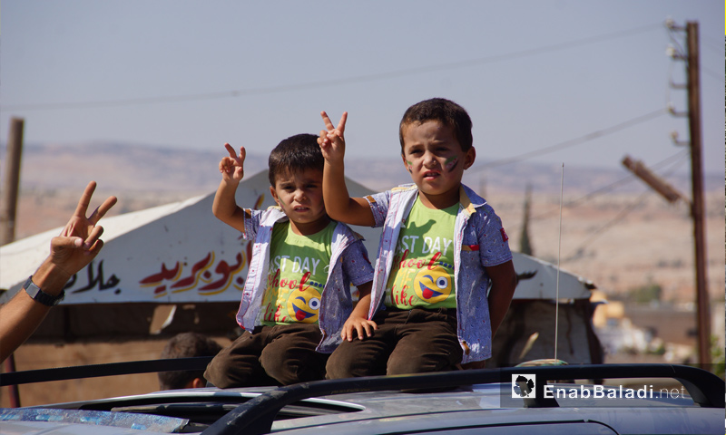 طفلان يشاركان في المظاهرات الرافضة للتدخل الروسي في إدلب -31 من آب 2018 (عنب بلدي)