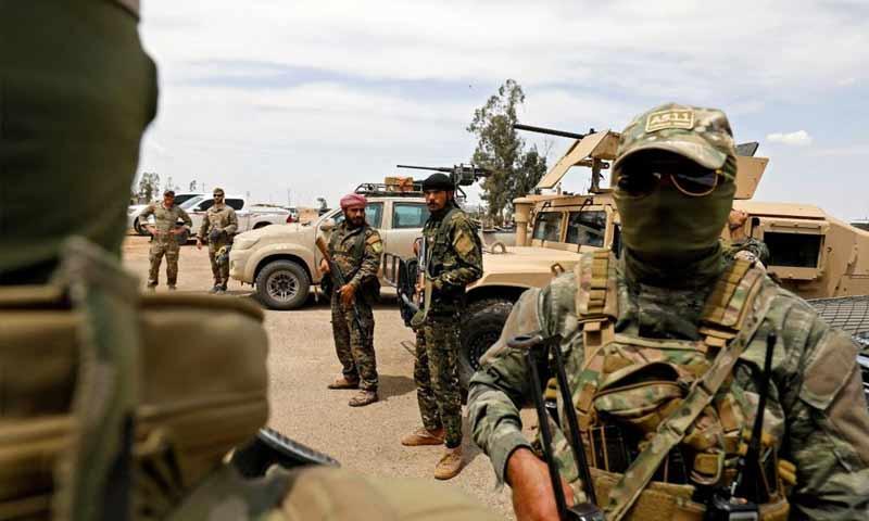 """جنود أمريكا ومقاتلون من """"قوات سوريا الديمقراطية"""" في حقل التنك النفطي شرق دير الزور - 1 أيار 2018 (AFP)"""