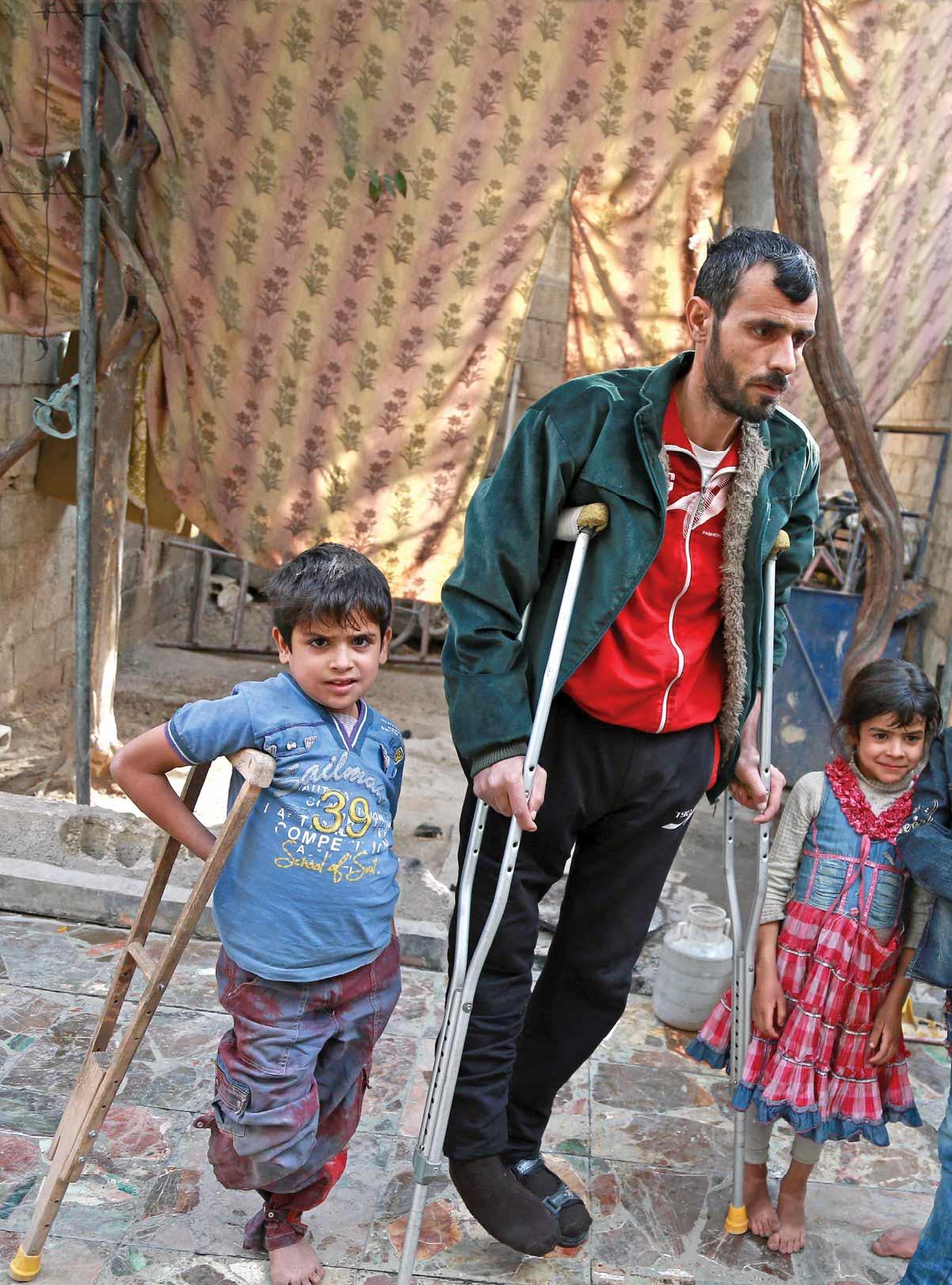 رجل مصاب مع أطفاله في حمورية بريف دمشق - 24 كانون الثاني 2017 (SAMS)