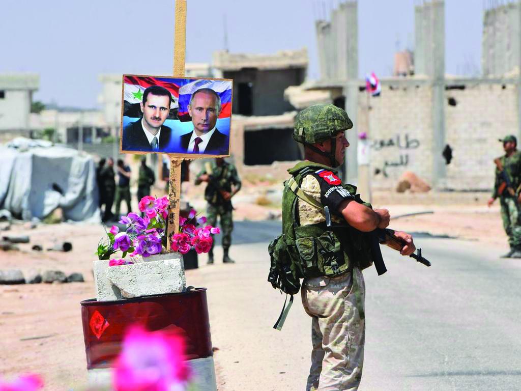 عناصر من القوات الروسية يقفون بالقرب من ملصقات رئيس النظام السوري بشار الأسد الرئيس الروسي فلاديمير بوتين شرقي محافظة إدلب - 20 آب 2018 (Getty)