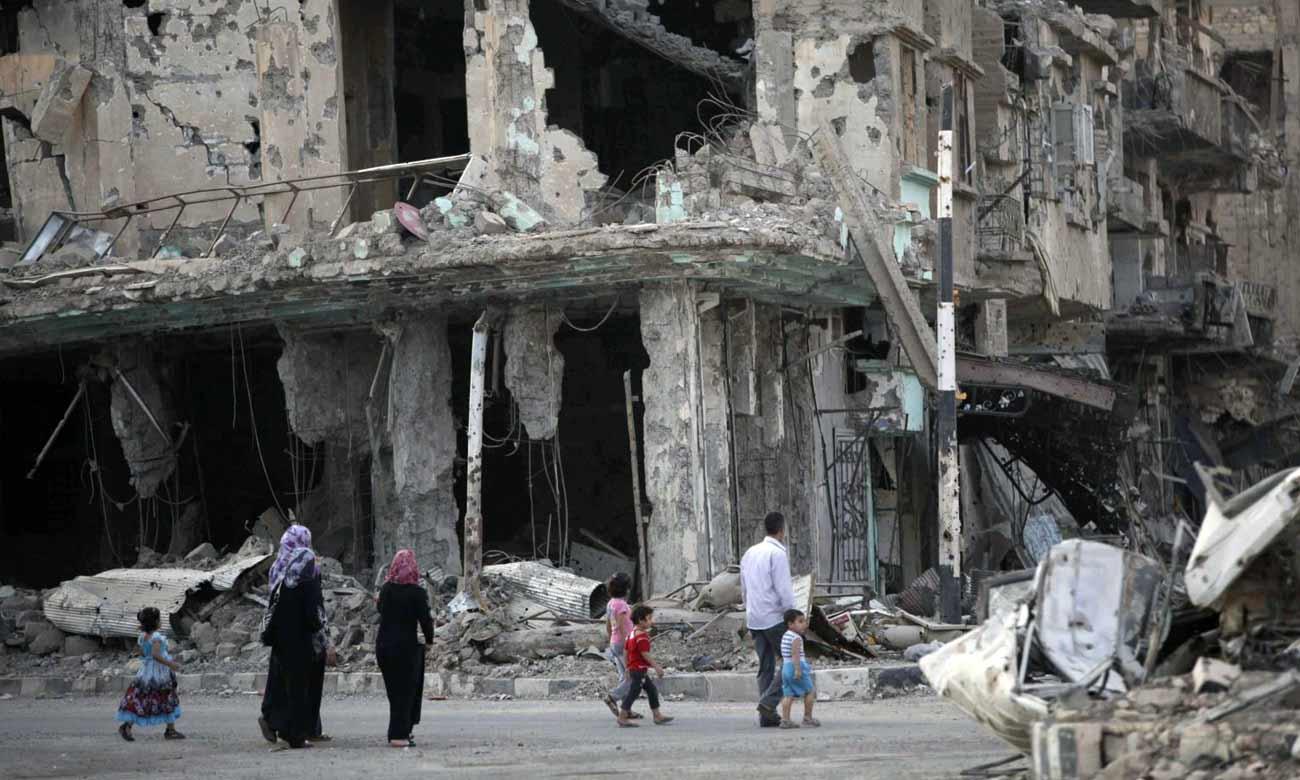 سوروين يمشون ضمن الدمار في دير الزور (رويترز)
