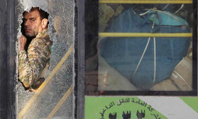 مقاتل من كفريا والفوعة في أثناء خروجه من إدلب بموجب اتفاق إيران مع تحرير الشام - تموز 2018 (رويترز)