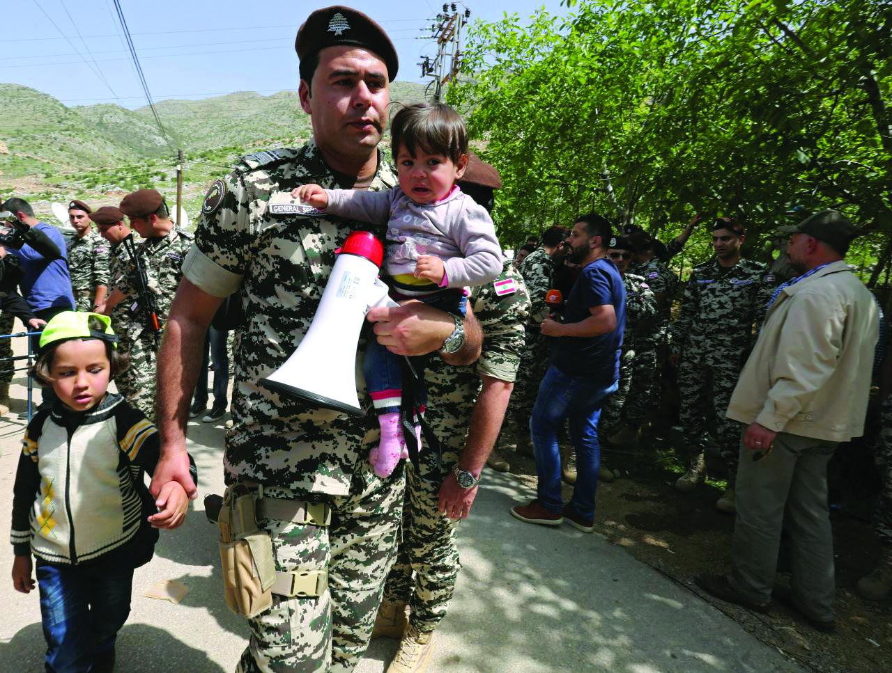 عضو الأمن العام اللبناني مع أطفال سوريين لاجئين وهم ينتظرون عودة الحافلات إلى سوريا - لبنان في 18 نيسان 2018 (رويترز)
