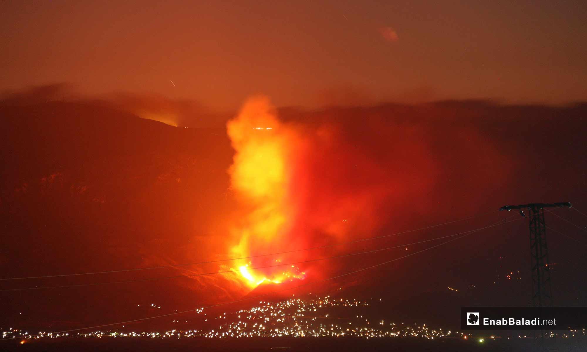 صورة ملتقطة من قرية كفر عويد تظهر حريق في معسكر جورين بسهل الغاب غربي حماة إثر قصف لفصائل المعارضة - 5 أيلول 2018 (عنب بلدي)