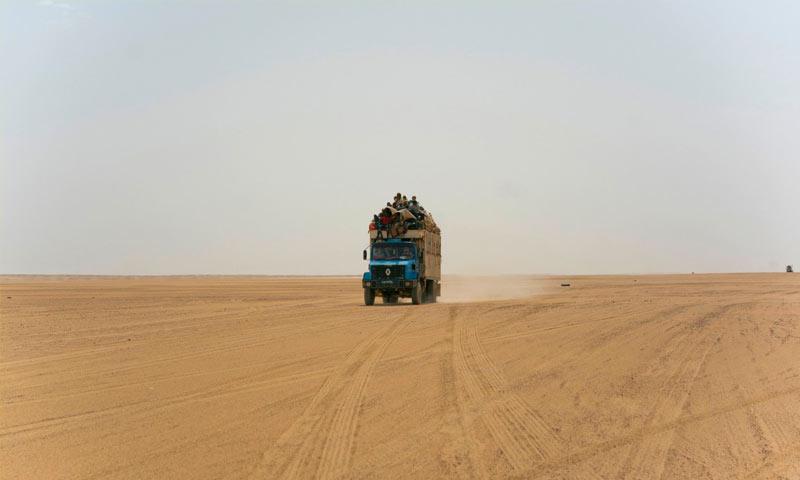 شاحنة تحمل بضائع ومهاجرين تسير عبر صحراء تنير النيجيرية جنوبي الصحراء الوسطى (AP)