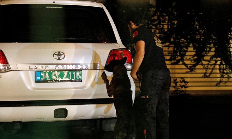 الشرطة التركية مع كلب بوليسي يفحص الفناء الخلفي للمقر العام للملك السعودى محمد العتيبي - 19 تشرين الأول 2018 (رويترز)
