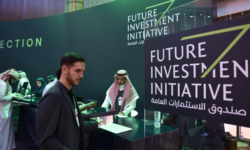 صحفيون يحصلون على بطاقاتهم من المركز الصحفي لمنتدى الاستثمار في الرياض (AFP)