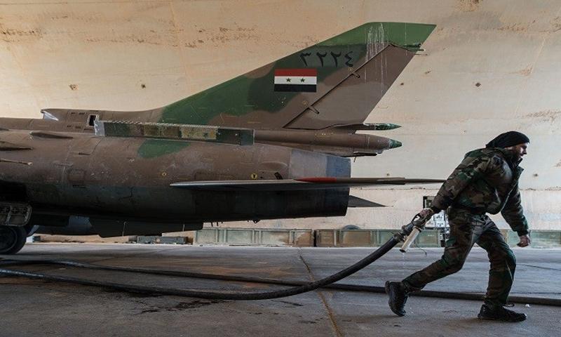 عنصر من قوات الأسد يعمل على تجهيز طائرة حربية نوع ميغ في مطار تي فور بريف حمص في سوريا - (انترنت)