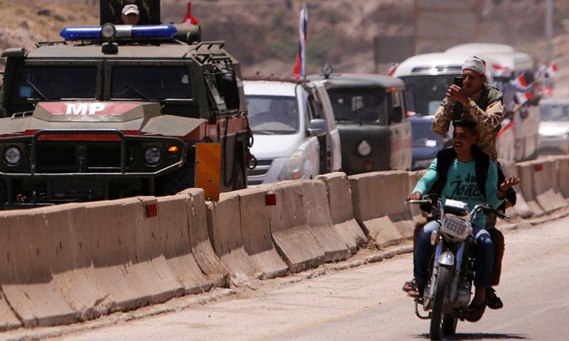 جندي سوري يأخذ صورًا شخصية بالقرب من مركبة عسكرية روسية في قافلة أثناء إعادة فتح الطريق بين حمص وحماة - حزيرن 2018 - (رويترز)