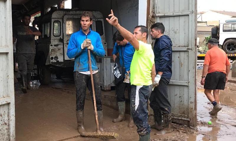 لاعب التنس العالمي رافائيل نادال خلال مساعدته لأهالي إقليم مايوركا في تنظيف ما خربه الفيضان (رافائيل بلازا)