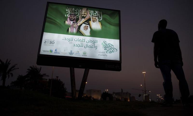 أحد المشاة يقف أمام لافتة مضاءة فيها صور العائلة الملكية في الظهران بالمملكة العربية السعودية (بلومبيرغ)