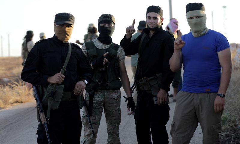 """مقاتلون من """"هيئة تحرير الشام"""" يرفعون راية التوحيد على مدخل كفريا والفوعة - تموز 2018 (رويترز)"""