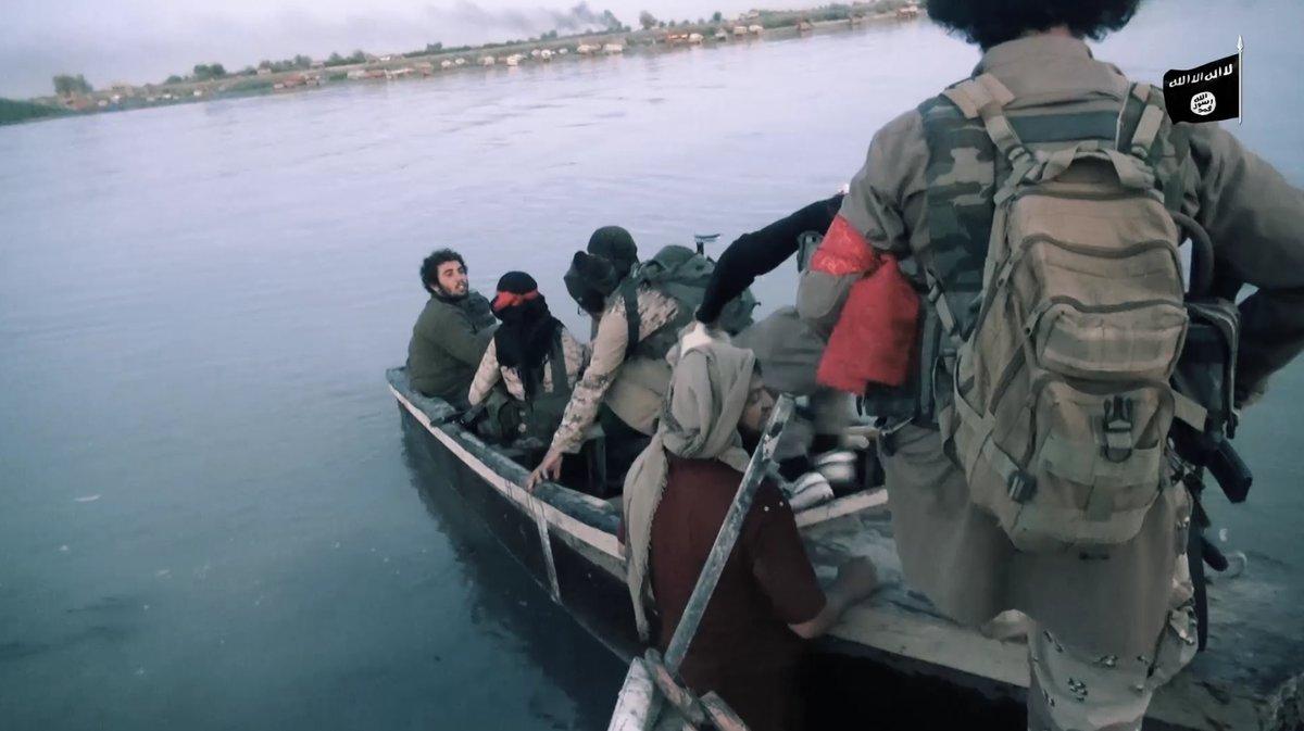 عناصر من تنظيم الدولة في أثناء عبورهم بالقوارب من نهر الفرات - (أعماق)
