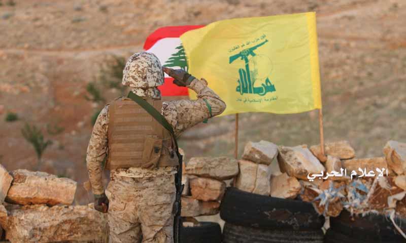 مقاتل من حزب الله اللبناني أمام العلم اللبناني وراية الحزب جنوبي لبنان (الاعلام الحربي)