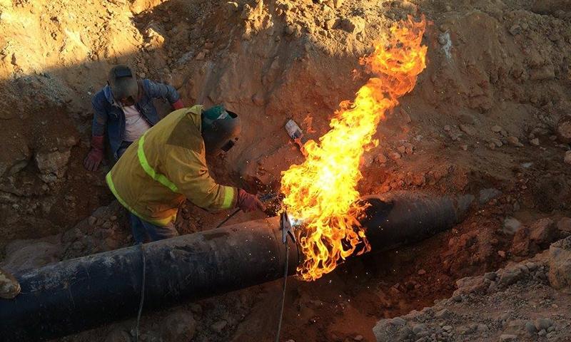 عمال في وزارة النفط السورية يعملون على صيانة أنابيب النفط (رئاسة مجلس الوزراء)