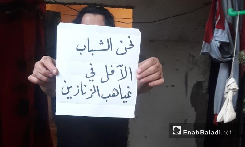 معتقل يرفع لافتة في سجن حماة رفضًا لأحكام الإعدام - 12 من تشرين الثاني 2018 (عنب بلدي)