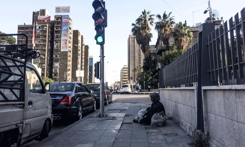 امرأة متسولة في شارع الثورة بدمشق (فيس بوك عدسة شاب دمشقي)