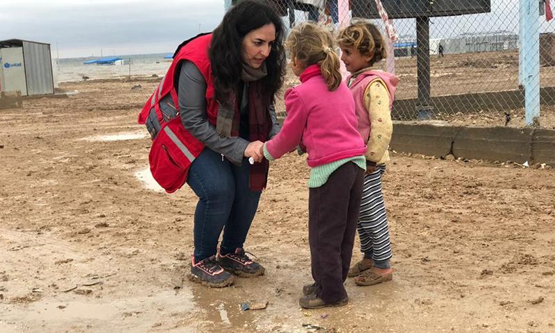 """متطوع لدى """"الصليب الأحمر"""" مع أطفال في مخيم العريشة بريف الحسكة الجنوبي-كانون الاول 2018 (الصليب الأحمر)"""