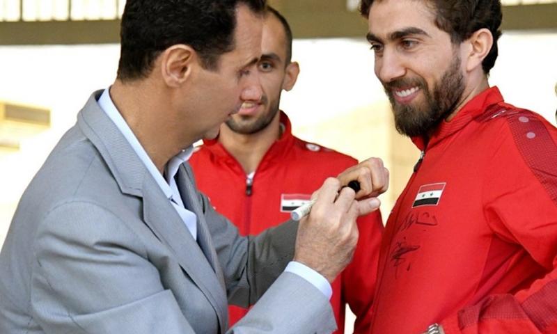 رئيس النظام السوري، يوقع على قميص اللاعب فراس الخطيب (سانا)