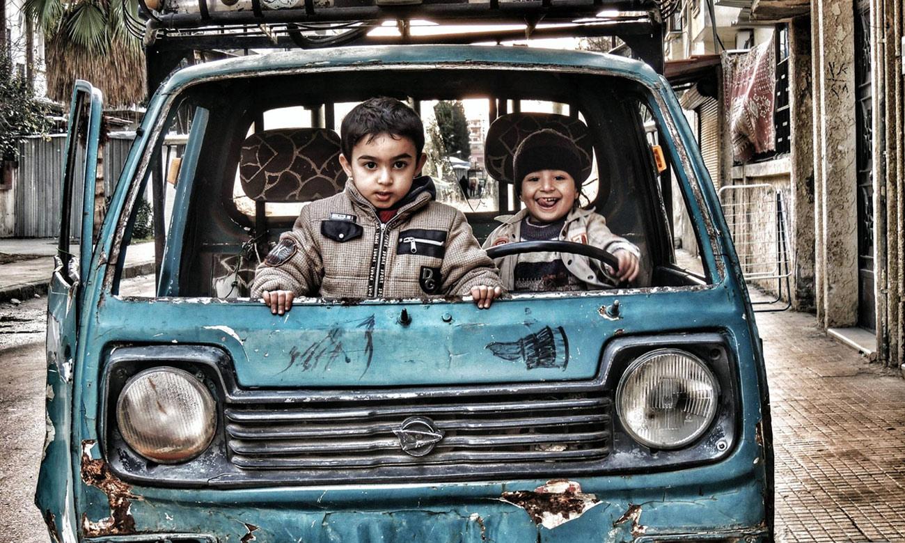أطفال يلهون بسيارة معطلة في حي الوعر بحمص - 6 كانون الثاني 2015 (عدسة شاب حمصي)