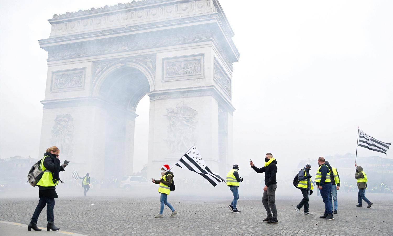 متظاهرون في مدينة باريس قرب قوس النصر في ظل إطلاق الشرطة الرصاص المسيل للدموع - 1 كانون الأول 2018 (رويترز)