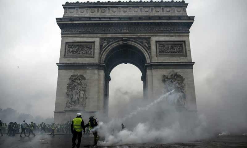 متظاهرون يتواجهون مع شرطة مكافحة الشغب لدى قوس النصر في باريس 1 كانون الاول 2018 (فرانس برس)