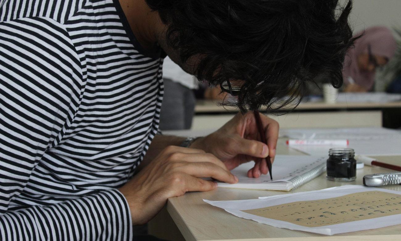 طالب يتدرب على الخط العربي في اسطنبول التركية - 27 حزيران 2018 (صالون مرحبا الثقافي)