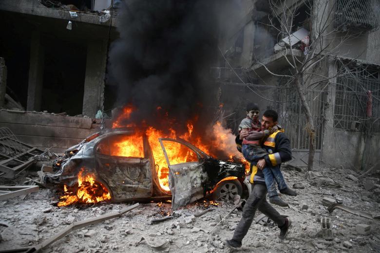 """رجل من عناصر """"الدفاع المدني"""" ينقذ طفل في قصف استهدف مدينة حمورية (رويترز)"""