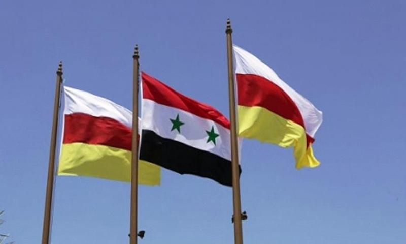 علم جمهورية أوسيتيا الجنوبية وعلم سوريا في العاصمة الأوسيتية تسخينفال (cominf)