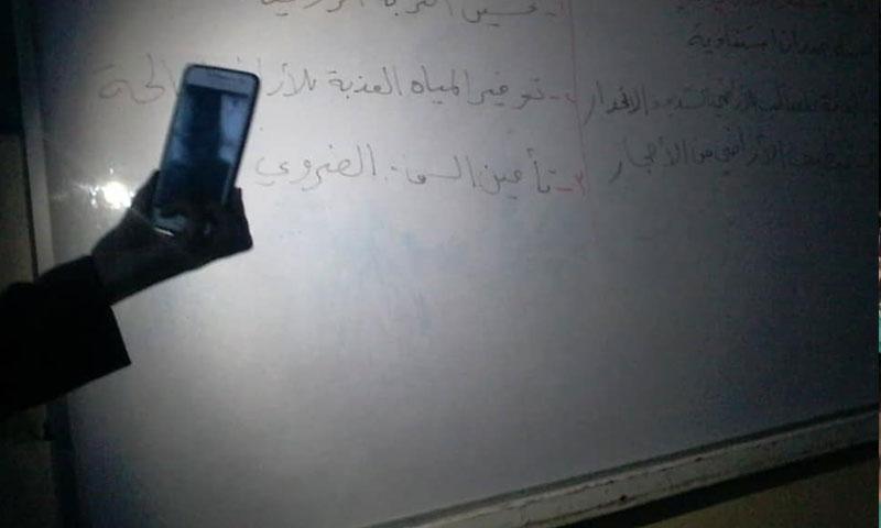 معلم يعطي الدرس للتلاميذ على ضوء الهاتف بسبب انقطاع الكهرباء في حلب (فيس بوك)