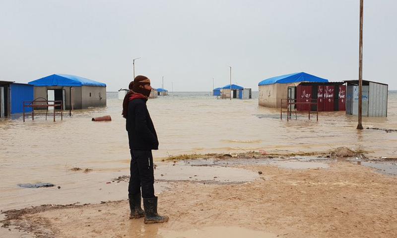 نازح في مخيم العريشة جنوبي الحسكة، ينظر إلى المياه التي غمرت الخيام - 6 كانون الأول 2018 (UNSYRIA)