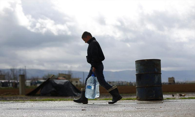 تعبيرية: طفل سوري يحمل عبوات مياه في مخيم الفيضاء شرق بيروت (AP)
