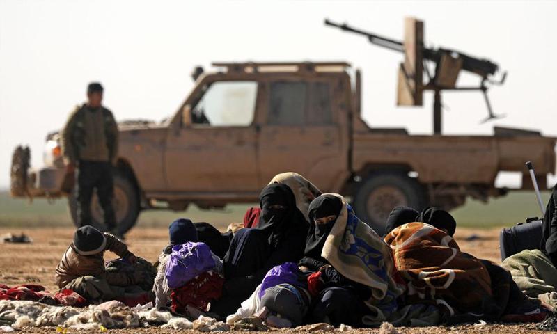مدنيون يهربون من القتال ضد تنظيم الدولة شرق الفرات وخلفهم مقاتل من قسد 3 شباط 2019 (دليل سليمان / AFP)