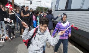 طفل لاجئ يلوح بالعلم الدنماركي (رويترز)