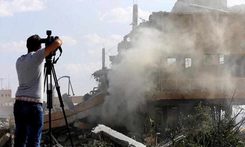 مصور سوري يلتقط صورًا لآثار قصف استهدف مركز البحوث العلمية شمال دمشق - نيسان 2018 (AFP)