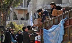 مقاتلون من المعارضة يساعدون بتفريغ مساعدات إنسانية أممية في حمص - شباط 2014 (AFP)
