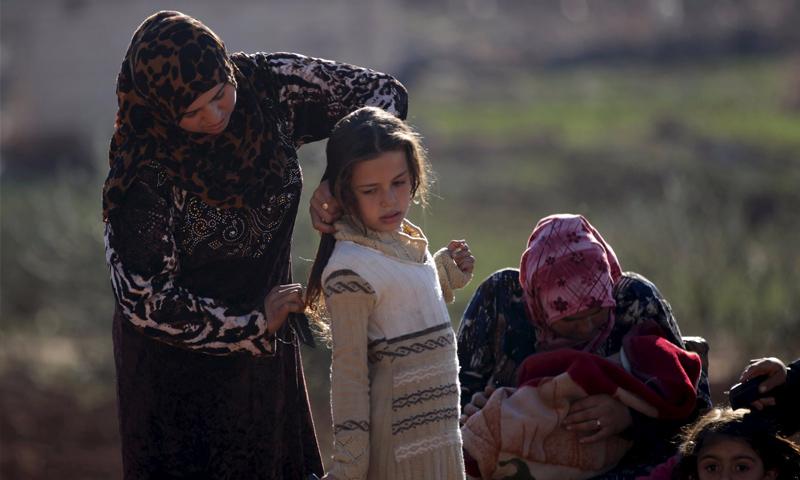 امرأة سورية نازحة داخلياً تمشط شعر ابنتها بالقرب من ملجأهم المؤقت - 26 كانون الأول 2015 (رويترز)