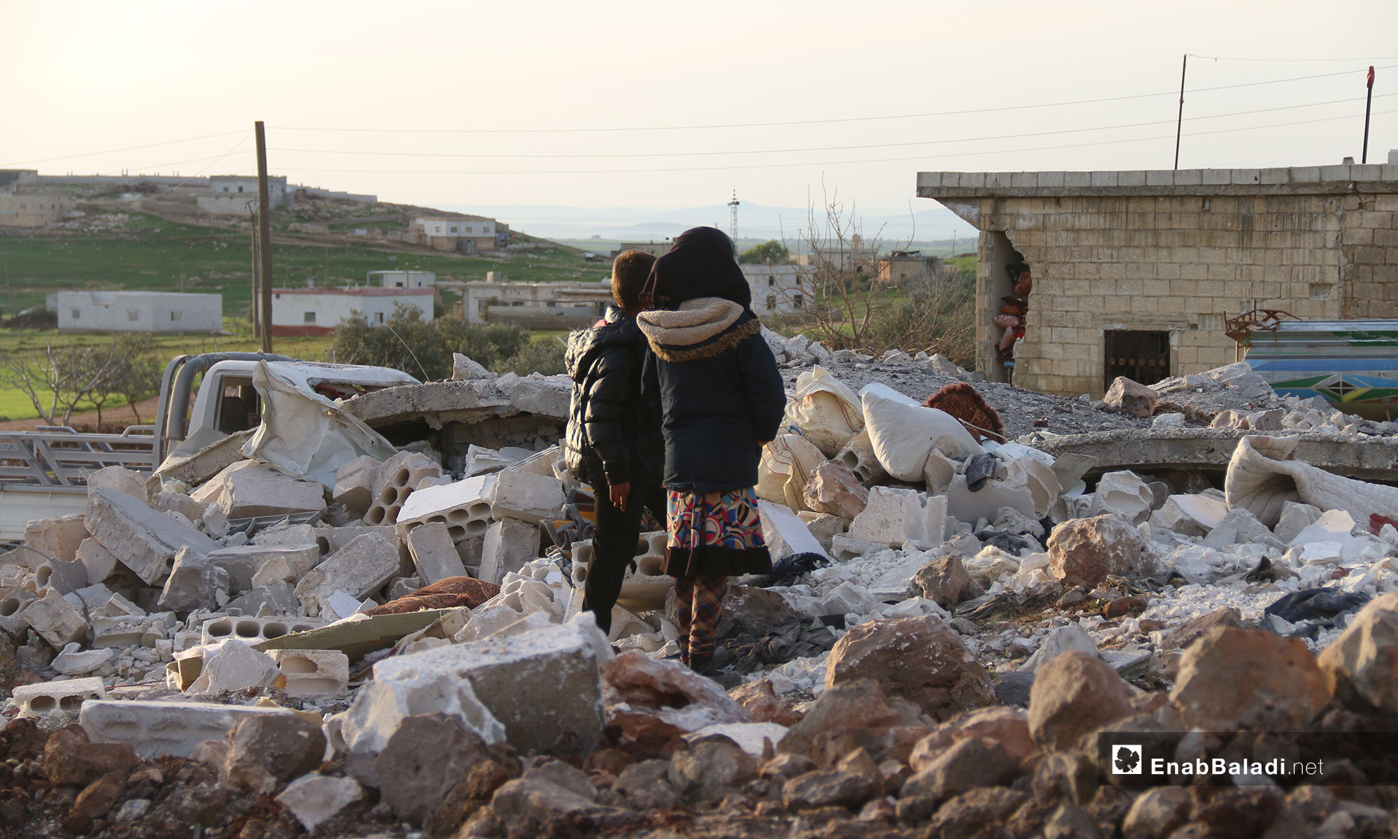 طفلان ينظران إلى ركام المنازل بعد قصف الطيران الروسي في بلدة الفقيع جنوبي إدلب - 21 من آذار 2019 (عنب بلدي)